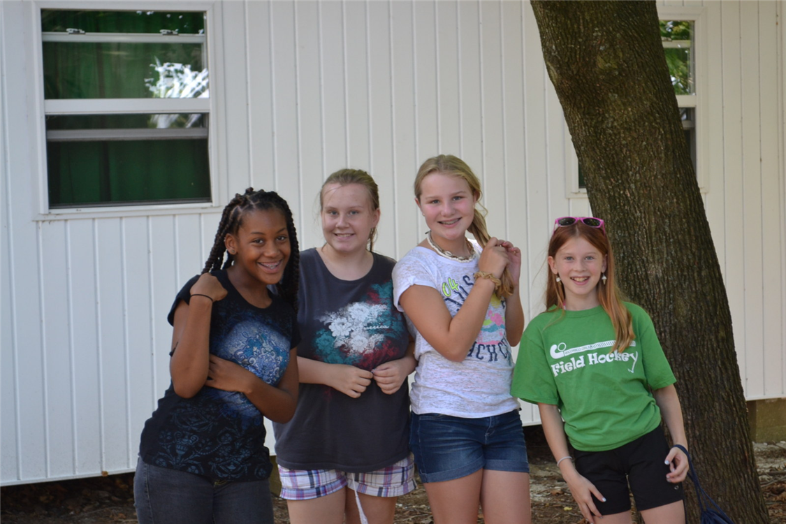 Campers post for a group picture outside their cabin.