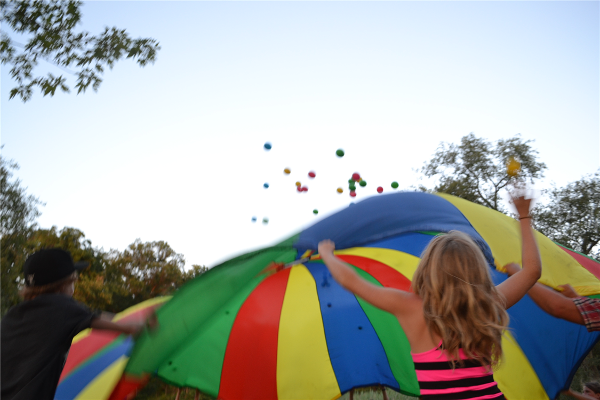 Campers enjoy time playing with the parachute during Field Games.