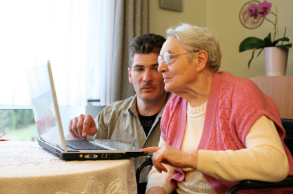 Elder Woman and Young Man at Laptop resized 600